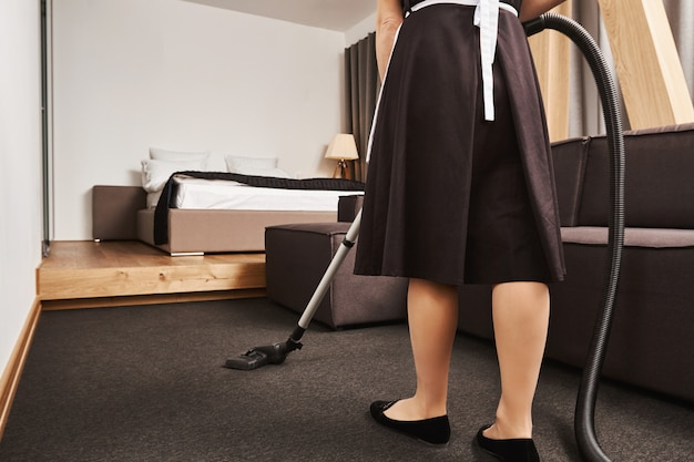 Cropped rearview of female housemaid cleaning floor of living room with vacuum cleaner, being busy and in hurry to finish before owner will come home, trying to remove all dirt and make apartment neat Free Photo