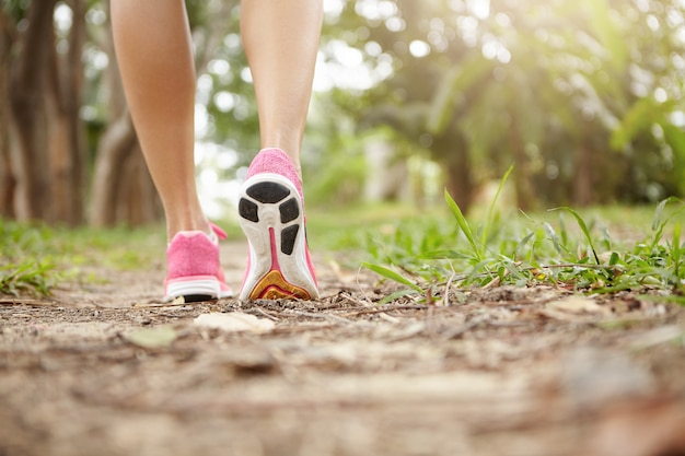 Cropped shot of athlete girl in pink running shoes hiking in forest on sunny day. fit slim legs of sporty female in sneakers during jogging workout. selective focus on sole. Free Photo