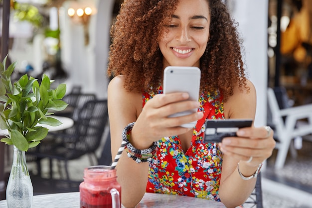 Cropped shot of beautiful african american woman with happy look, holds modern cell phone and credit card, makes shopping online Free Photo
