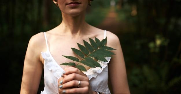Ritagliata colpo di bella giovane sposa tenera in abito bianco romantico in posa su sfondo verde foresta, che tiene foglia di felce al petto. femmina irriconoscibile rilassante all'aperto tra le piante Foto Gratuite