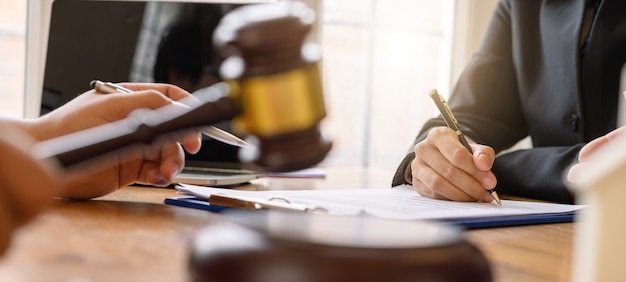 Cropped shot of business people and lawyer or judge team discussing signing contract, concepts of law, advice, legal services. Premium Photo