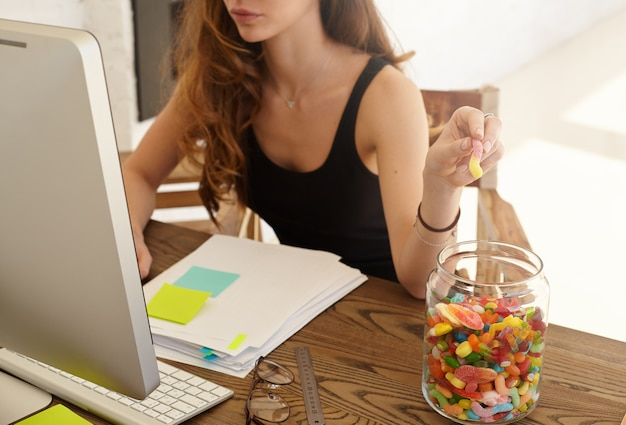 Cropped shot of the caucasian female office worker taking marmalade from the big jar at work. the girl eats candies for improvement of work of a brain during hard work over the financial statement Free Photo