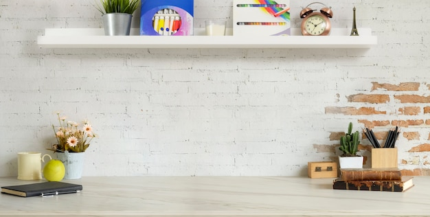 Cropped shot of comfortable designer workplace with office supplies and copy space on marble desk and brick wall Premium Photo