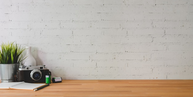 Cropped shot of comfortable workplace with camera and office supplies on wooden table and brick wall Premium Photo