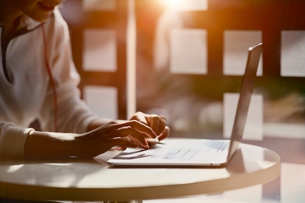 Cropped shot of female hand  typing on her laptop at home studio workplace Premium Photo