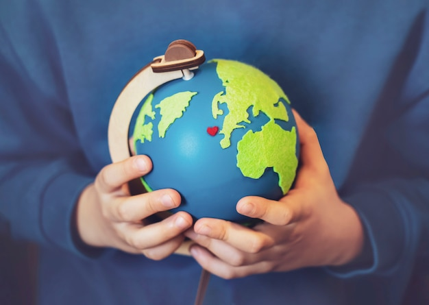 彼の手で地球を保持している少年のショットをトリミングしました。地図、4月22日の地球の日、緑の世界環境の日の概念に赤いハートのグローブを手 Premium写真