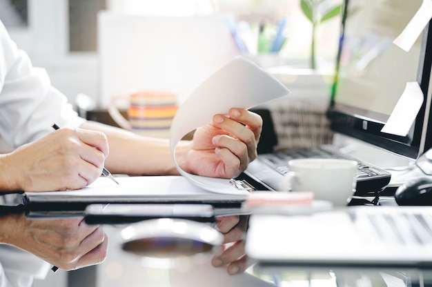 Cropped shot of man hand using pencil writing on clipboard while sitting at office desk and working with computer. Premium Photo