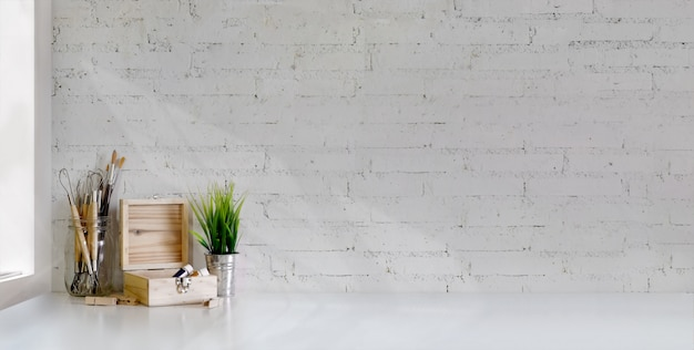 Cropped shot of minimal artist workplace with painting tools on white table and white brick wall Premium Photo