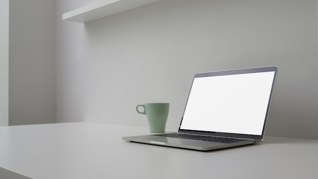 Cropped shot of minimal workspace with open blank screen laptop, mug and copy space Premium Photo