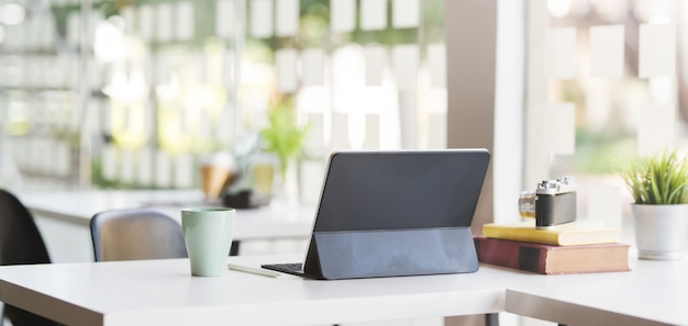 Cropped shot of modern office room with blank screen tablet, camera and office supplies Premium Photo