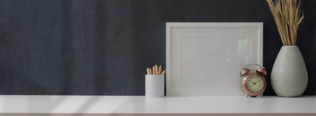 Cropped shot of modern workplace with mock up frame and office supplies Premium Photo