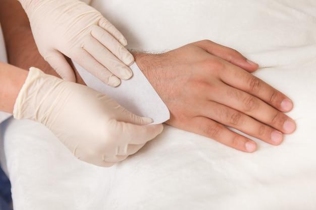 Обрезанный снимок косметолога, делающего воск на руке клиента-мужчины Premium Фотографии
