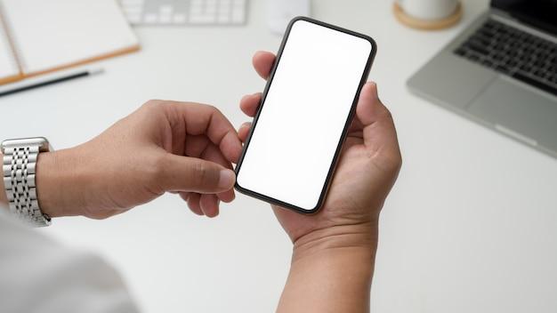 Обрезанный снимок бизнесмена, держа пустой экран смартфона на белом столе Premium Фотографии