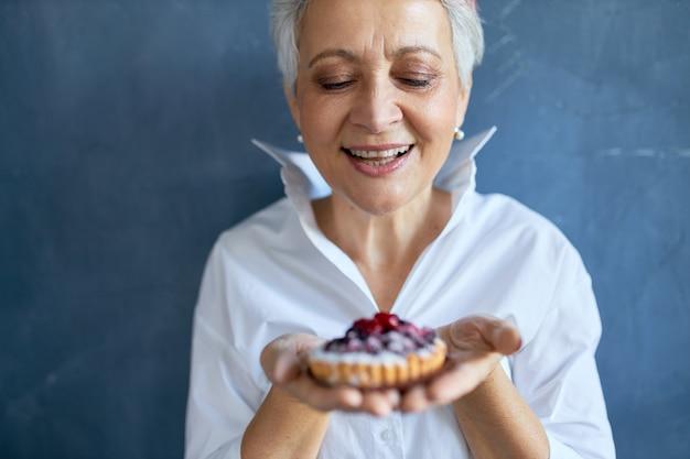 생일을 위해 갓 구운 베리 파이 조각을 들고 흰 셔츠에 쾌활한 매력적인 할머니의 자른 샷, 즐거운 표정, 광범위하게 웃고. 무료 사진