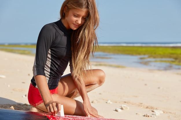Обрезанный снимок восхищенной стройной женщины, натирающей доску для серфинга воском для безопасного серфинга и защиты от падений Бесплатные Фотографии