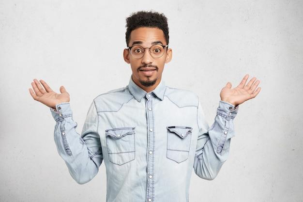 Обрезанный снимок модного молодого мужчины в джинсовой одежде и очках, жесты руками Бесплатные Фотографии