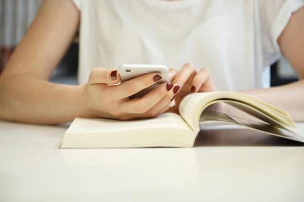 Обрезанный снимок женщины с аккуратным маникюром в белой блузке, положив руки на открытую книгу, просматривая интернет с помощью мобильного телефона во время учебы и поиска информации в библиотеке Бесплатные Фотографии