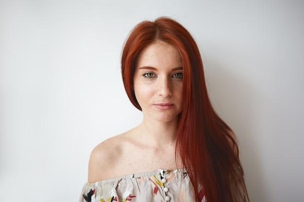 Обрезанный снимок великолепной красивой молодой кавказской женщины с рыжими волосами, веснушчатым лицом и плечом, позирующей на пустой стене пространства для копирования, одетой в романтический летний цветочный топ. красота, стиль и мода Бесплатные Фотографии