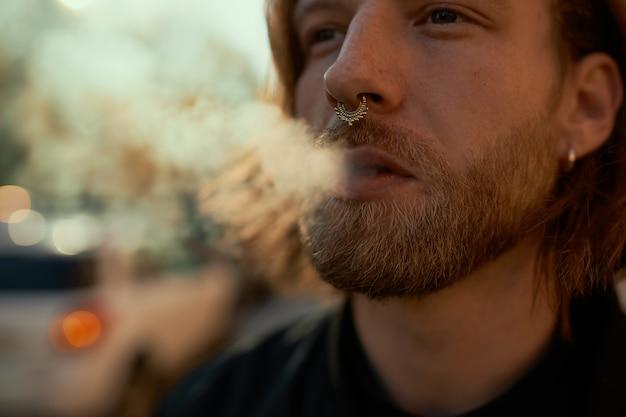잘 생긴 세련 된 젊은 수염 된 남성 Vaping 전자 담배 야외의 자른 된 샷. 화창한 여름 날에 도시 거리를 걷는 동안 코걸이 연기가 나는 매력적인 남자의 닫기 무료 사진