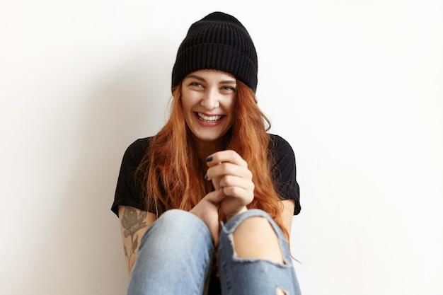スタイリッシュな黒い帽子、tシャツ、ボロボロのブルージーンズを着て、ゆるい生姜髪の幸せな女の子のショットをトリミング 無料写真