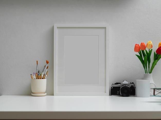 모의 프레임, 페인트 브러시, 카메라, 꽃병 및 복사 공간이있는 홈 오피스의 자른 샷 프리미엄 사진