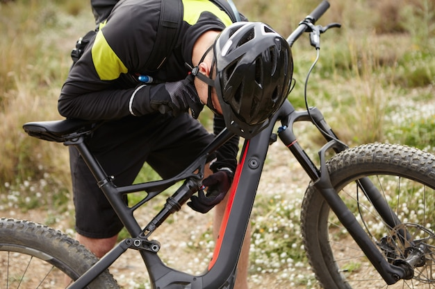 Обрезанный снимок байкера мужского пола в шлеме и перчатках, проверяющих системы на черном электронном велосипеде, наклонившись вперед над его двухколесным моторным транспортным средством. молодой велосипедист ремонтирует или фиксирует pedelec в лесу Бесплатные Фотографии