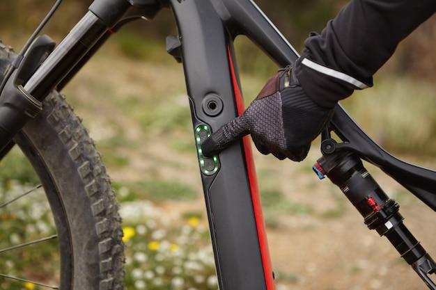 電動自転車のコントロールパネルの人差し指でボタンを押すと黒い手袋の男性の手のショットをトリミングしました。バイカーがモーター式ブースター自転車を上り坂で走行する前に速度モードを切り替える 無料写真