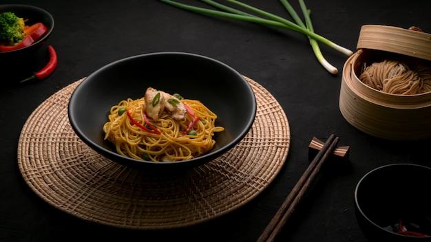 シェズワンヌードルのクロップドショット、野菜、チキン、チリソース添え Premium写真