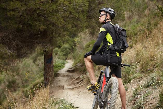 Обрезанный снимок стильного профессионального байкера в спортивной одежде, шлеме и очках, отдыхающих посреди леса, с черным электрическим велосипедом с электроприводом, любуясь красивой дикой природой вокруг него Бесплатные Фотографии