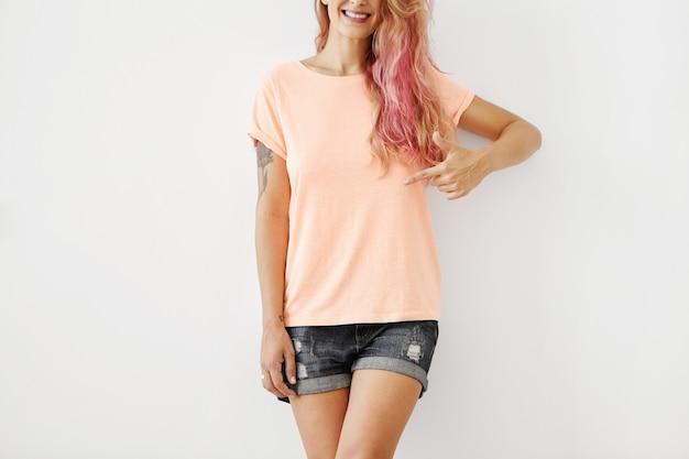 Обрезанный снимок стильной улыбающейся женщины в свободной футболке и джинсовых шортах, указывая на пустую футболку Бесплатные Фотографии