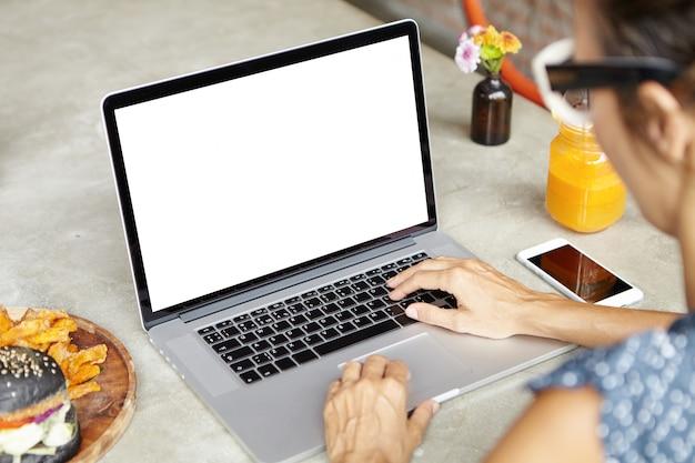 노트북 컴퓨터를 사용하여 휴일에 성공적인 여성 기업가의 자른 샷, 이메일 확인, 온라인 친구 메시징, 열린 노트북으로 카페에 앉아 무료 사진