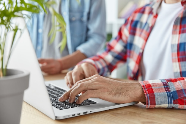 2人の男性ブロガーのクロップドショットは、ラップトップコンピューターで出版物を入力し、ラップトップコンピューターを使用し、木製の机に座っています。若い繁栄しているビジネスマンは、wifiに接続して、メールをチェックし、フィードバックを送信します 無料写真