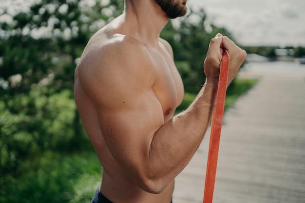 인식 할 수없는 근육질 남자의 자른 샷은 운동 팔뚝 운동이 강한 근육을 보여줍니다. 프리미엄 사진