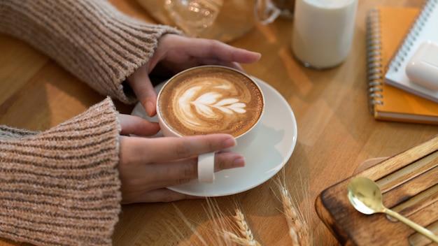 文房具と木製のテーブルでラテアートコーヒーを保持している若い女性のショットをトリミング Premium写真