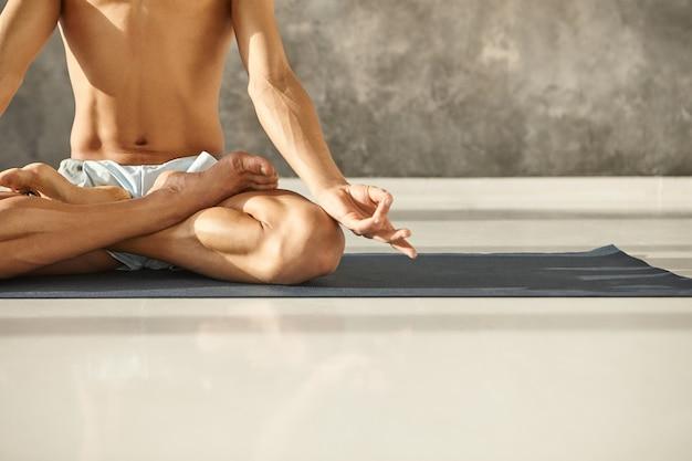 근육질 몸통과 팔을 Padmasana에 앉아 Mudra 제스처를 만드는 젊은 남성의 자른 샷. 로터스 포즈에서 매트에 요가 연습하는 인식 할 수없는 남자. 명상, 집중력 및 건강 무료 사진