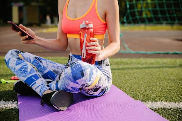 スポーツウェアの若い女性のトリミングされたショットはマットの上に座って、水を飲み、スマートフォンを使用しています。 Premium写真
