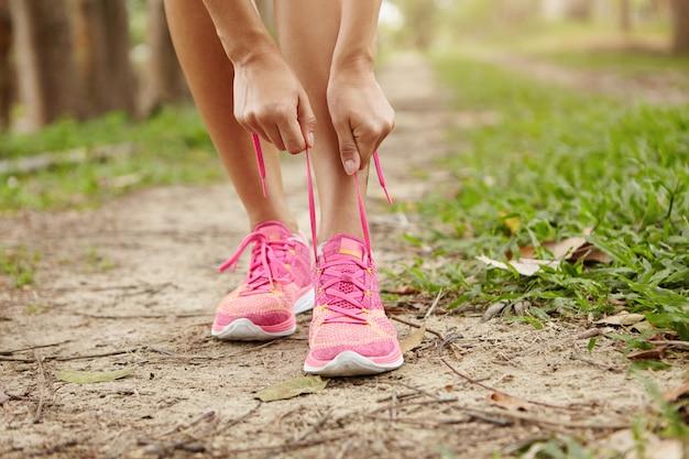 Обрезанный снимок бегуна молодой женщины затягивая шнурки кроссовок, готовится к бегу трусцой на открытом воздухе. Бесплатные Фотографии