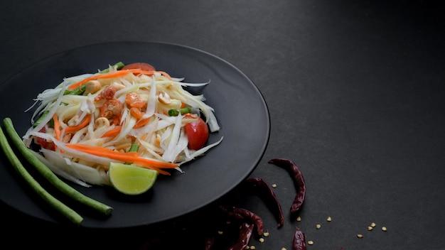 Cropped shot of papaya salad or somtum on black plate Premium Photo