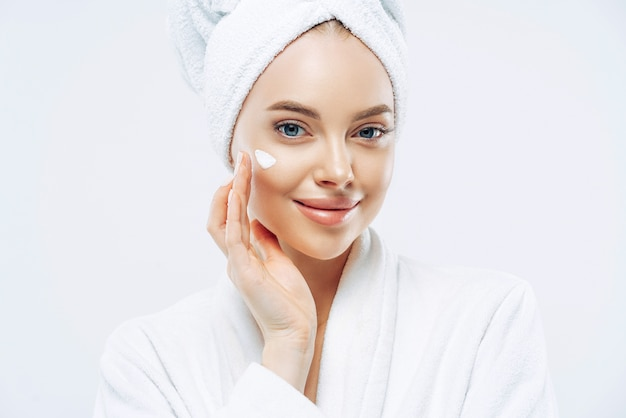 Cropped shot of pretty young woman applies cream for rejuvenation, healthy soft skin, uses cosmetic product, demonstrates nice effect of body lotion, wears comfortable soft white bath robe, towel Premium Photo