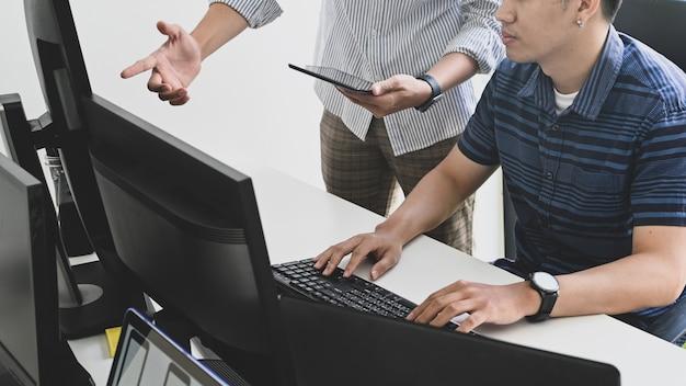 Обрезанный выстрел программист консалтинг с планшета и компьютера на рабочем месте разработчика. Premium Фотографии