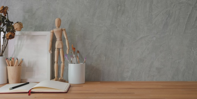 Cropped shot of trendy workplace with office supplies on wooden table and grey wall Premium Photo