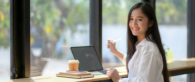 Cropped shot of university student sitting at coffee shop while working with tablet Premium Photo
