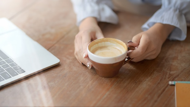 Cropped shot of a woman holding coffee cup in comfortable workplace Premium Photo