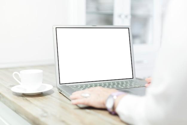 彼女の家で空白の画面でラップトップコンピューターを使用してトリミングされたショットの女性。 Premium写真