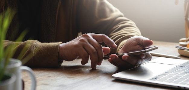 Cropped shot of young man using his smartphone while working on his project in comfortable office Premium Photo