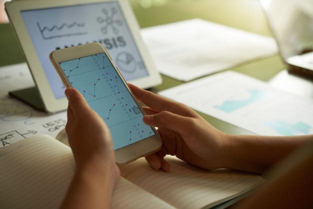 Обрезанный неузнаваемый человек, анализируя финансовые диаграммы на смартфоне Бесплатные Фотографии