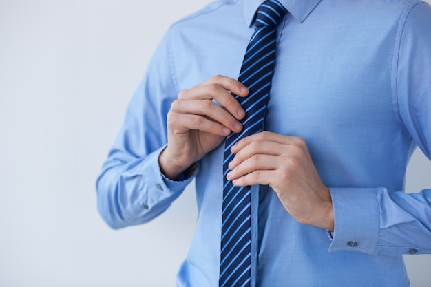 Cropped view of business leader adjusting tie Free Photo