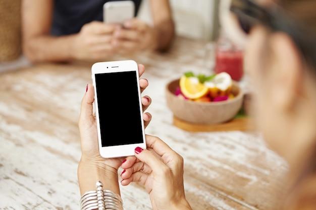 Vista ritagliata delle mani femminili con il manicure rosso che tiene il telefono cellulare con lo schermo vuoto. Foto Gratuite
