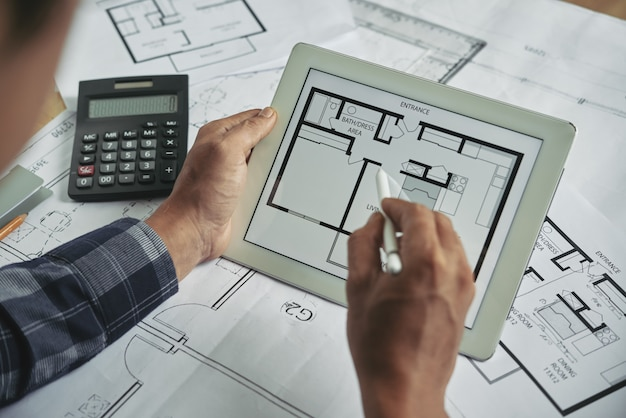 Cropped view of male hands holding the digital pad examining blueprint Free Photo