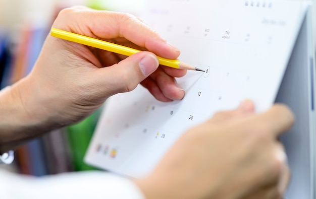 Cropped view of man hand holding yellow pencil writing on calendar. Premium Photo